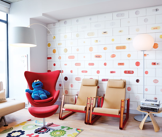 In the home office, loungers from DWR sit in front of a wall tiled with photos by Cindy Blaževic.