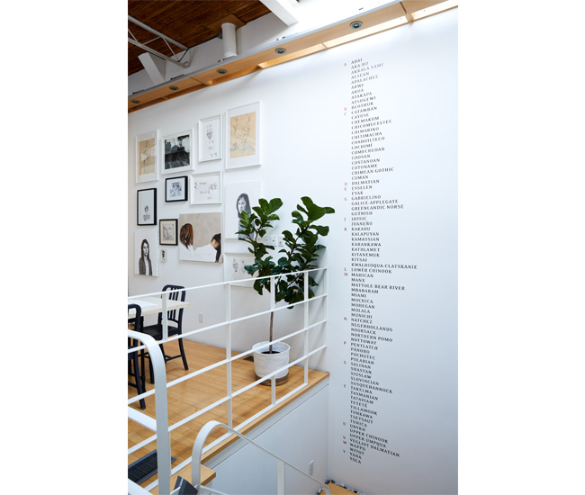 Illuminated by an overhead skylight, a stairwell-spanning mural by Carmen Dunjko lists a string of extinct languages.