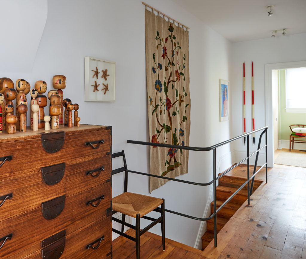 Custom steel tube railings lead upstairs where the curation continues. Here we find surveyors' poles, crewelwork and a Tansu chest topped with Kokeshi.