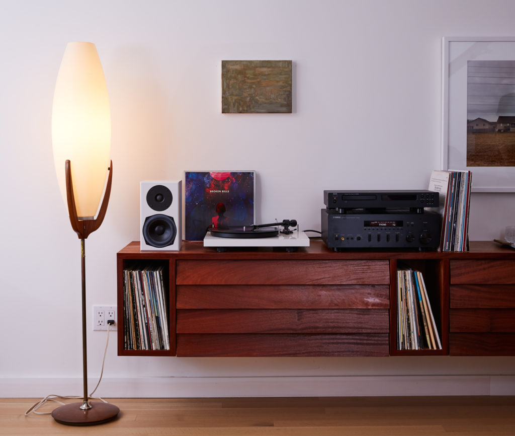 A matching wall-mounted cabinet (by Lynn) stores choice vinyl. Turntable and speaker from Bay Bloor Radio; the lamp is a vintage find.