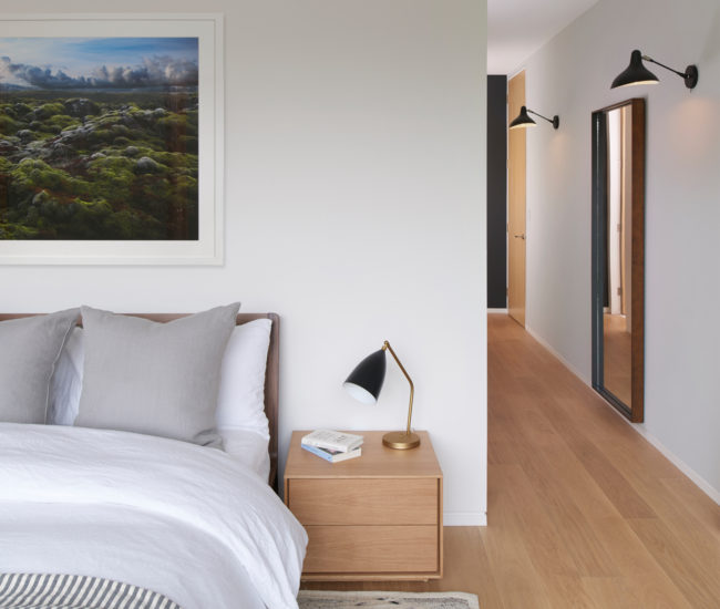Wall sconces from Design Within Reach light the master bedroom. Bed and nightstand from Urban Mode. Photo by Alex Lukey.