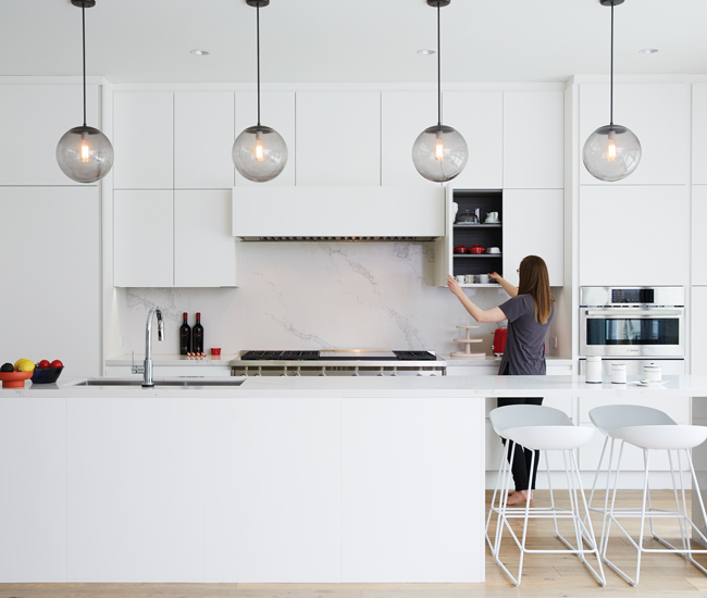 A Caesarstone-topped island anchors Trevisana cabinetry. Schoolhouse Electric pendants; stools from The Modern Shop; accessories from West Elm and Drake General Store.