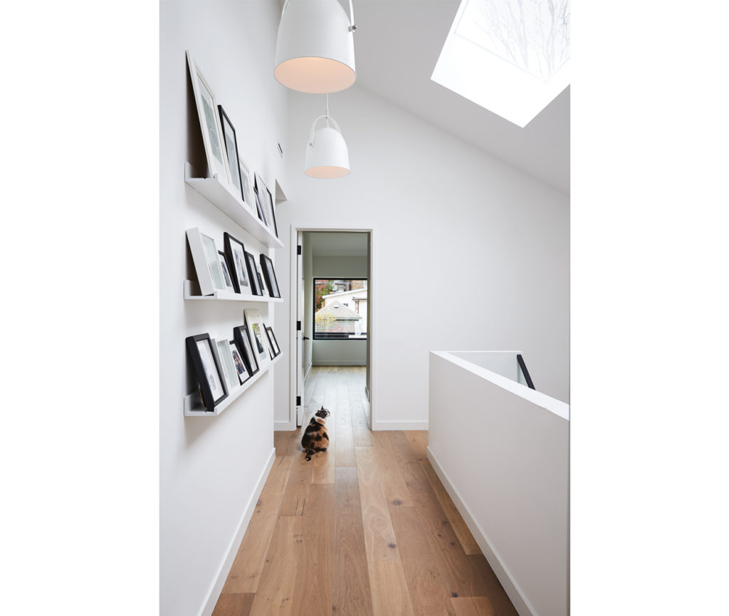 Family photos on Ikea picture rails create an art-gallery feel. Natural-oiled  oak throughout from Grebian Flooring Solutions; Article pendants; skylight from Artistic.