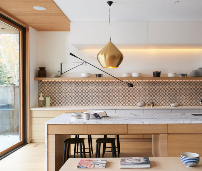 A graphic Stone Tile backsplash and jet black Coolican & Co. stools pop among the subdued Albatross millwork and Calacatta marble-topped island. Brass Tom Dixon pendant from Klaus. Photo by Alex Lukey.
