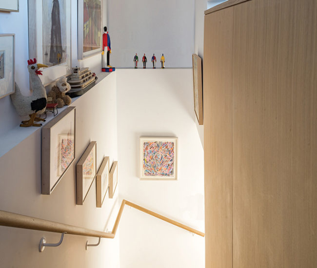 White oak handrails along the volumetric staircase are lit by recessed LEDs.