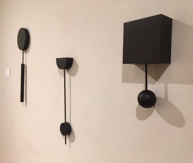 Pendulums by Lauren Reed. I thought they were clocks at first, but they have no internal mechanisms. You gently push them to begin and the pendulum swings on its own for quite a while. They are meant as objects for mediation rather than measurers of time.