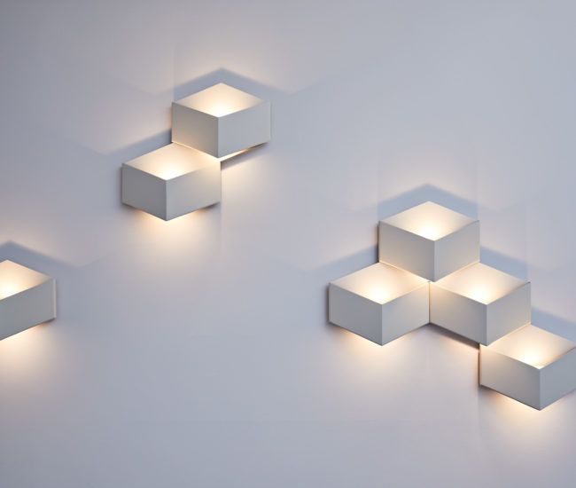 Lighting the way to the master bedroom are these folded metal sconces by Arik Levy for Vibia from LightForm.
