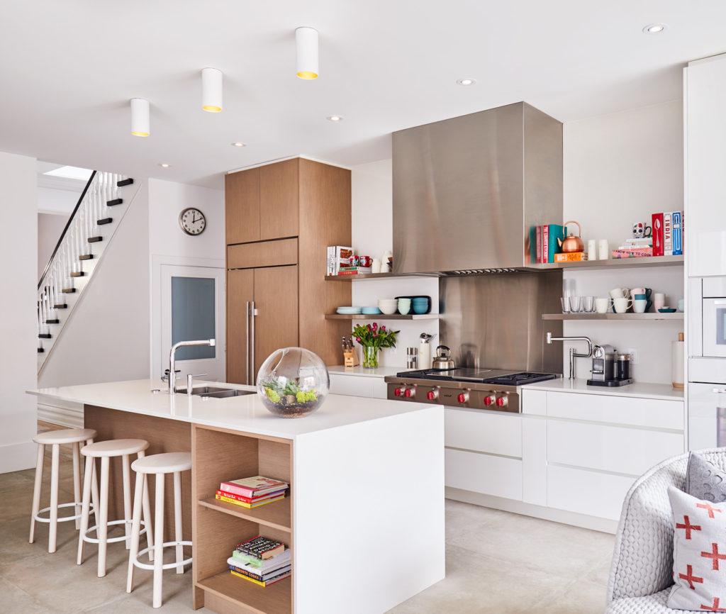 Formerly a series of small rooms, the now open-concept kitchen and family room features a system by Bellini Custom Cabinetry with a Caesarstone-clad island, Wolf appliances, heated concrete tiles from Stone Tile and stools by Herman Miller. Sofa from Klaus.