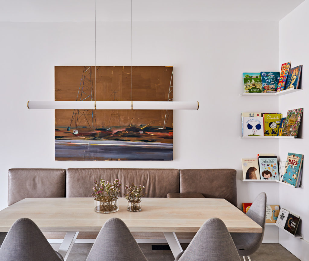 Above the custom-designed dining table with leather banquette hangs a Roll & Hill pendant from LightForm and art by Val Sears. Arne Jacobsen chairs from Torp Inc.