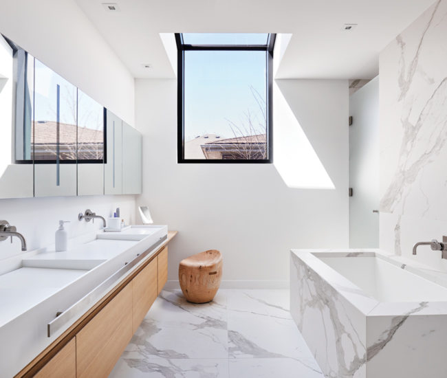 Another roof window bathes the master bath in sunlight. Porcelain slabs from Stone Tile; soaker tub from Ginger's; stool from Italinteriors.