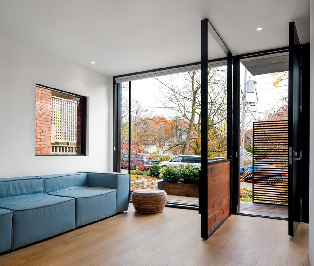 The entryway's steel frame features a thin tray for stashing keys, and supports a flat screen TV opposite the sofa.