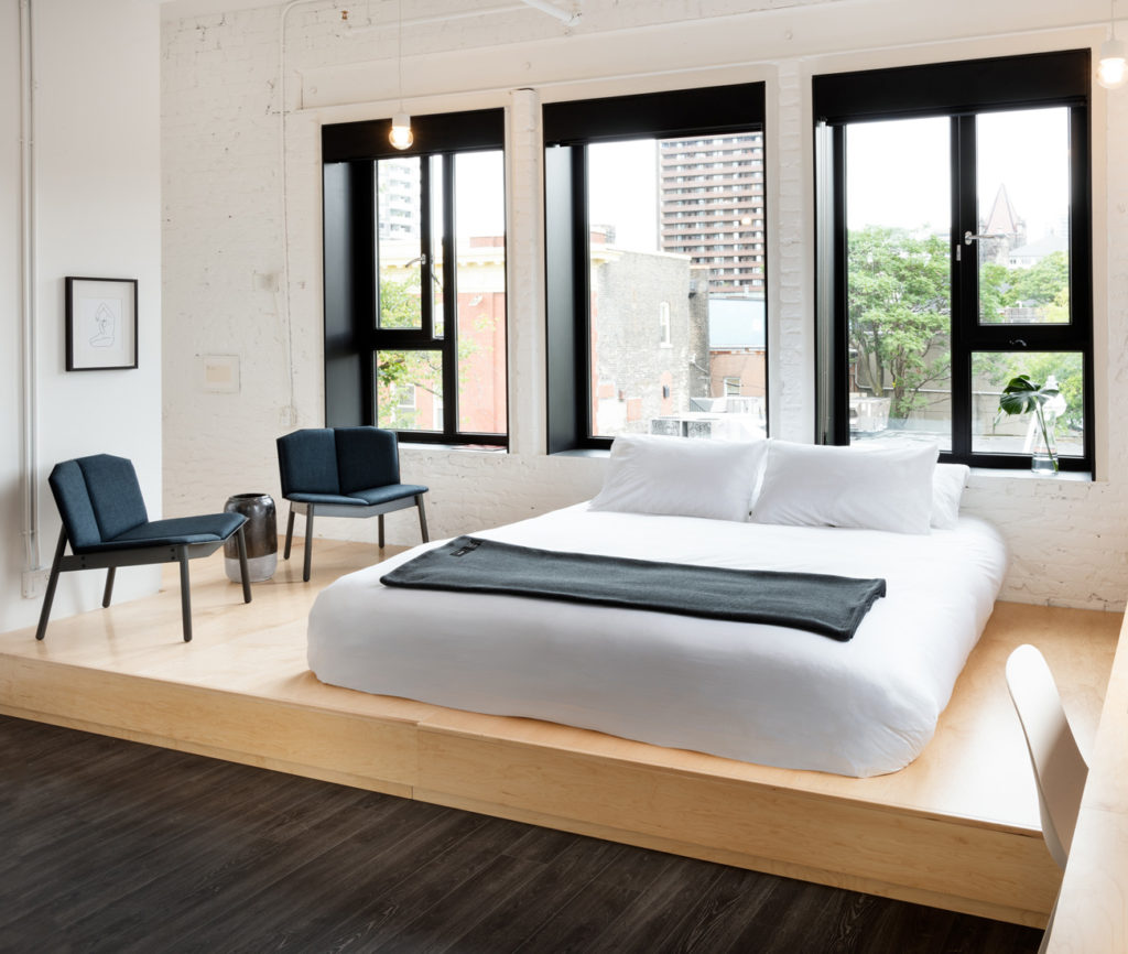 StudioAC's custom-designed platform bed (made by RDG Millwork) has built-in cubbies. Cats Pajamas chair by Blu Dot, at Urban Mode; Ikea pendants.