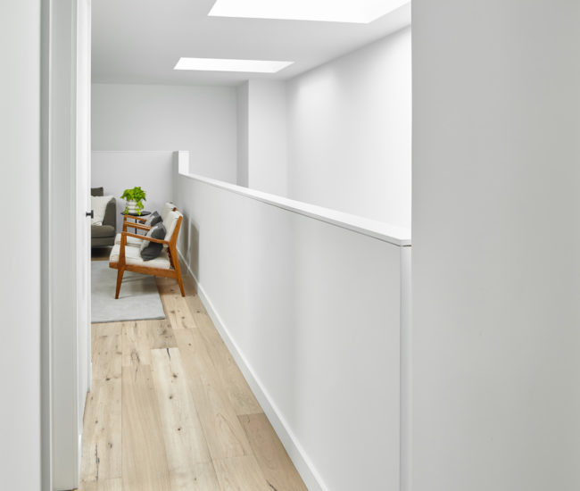 Skylights reign over the third-floor playroom, where an articulated corner and slots in the guardrails add interest to the space.